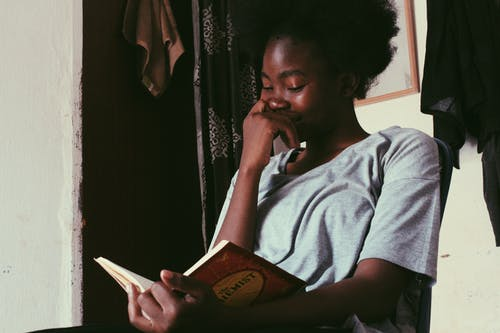 Young black woman with Afro hairstyle reading book