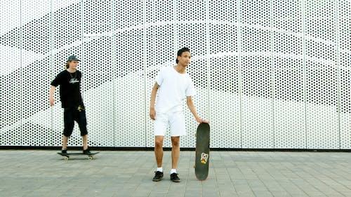 Man in White T-shirt and Black Pants Standing Beside Black Skateboard