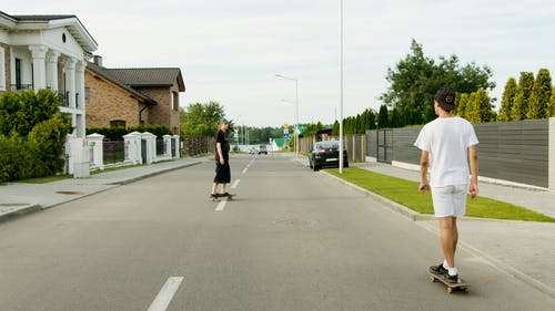 Man in Black T-shirt and Black Pants Walking on Sidewalk