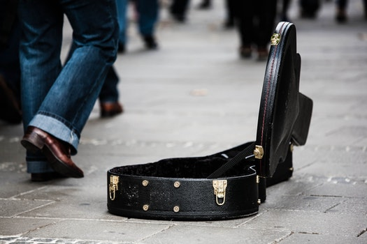 Black Guitar Case on Concrete Pathway With People Walking during Daytime