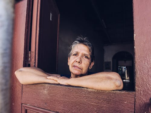 Elderly woman leaning on wooden framing