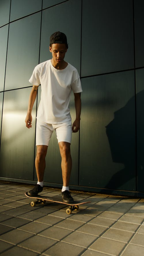 Man in White Crew Neck T-shirt and White Shorts Standing Beside Black Wooden Cabinet