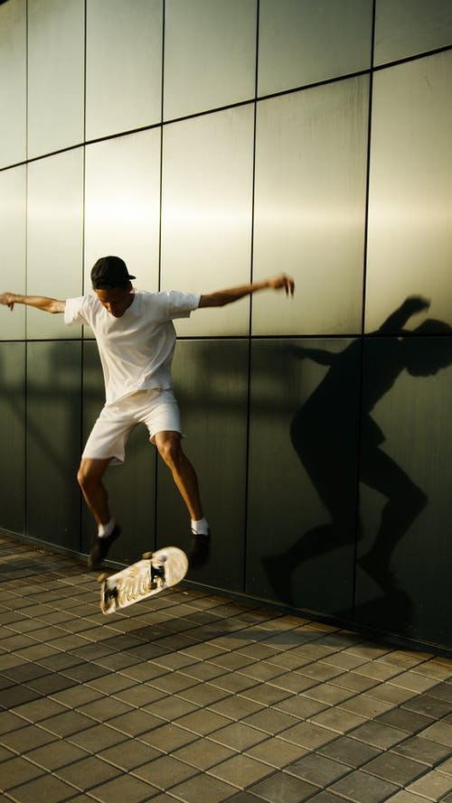 Man in White T-shirt and Brown Shorts Jumping on Brown Wooden Floor