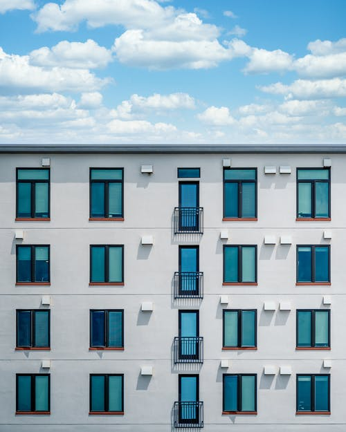 Facade of contemporary white building with blue windows and balconies under blue sky