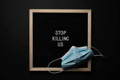 Top view of composition of blackboard with written phrase STOP KILLING US under mask against black background