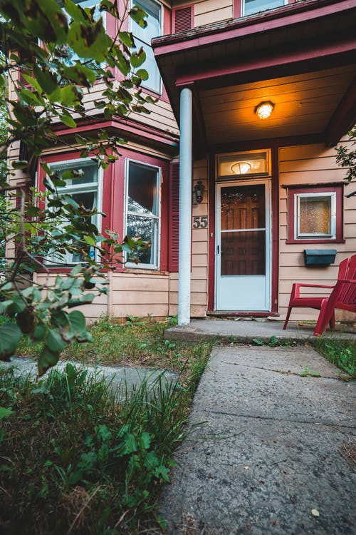 Low angle exterior of aged cozy residential cottage with geometric windows and green garden in yard