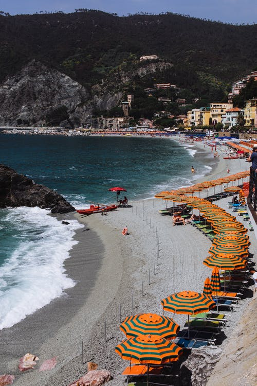 Amazing view of sandy beach with bright umbrellas and loungers and foamy water against rocky mountains