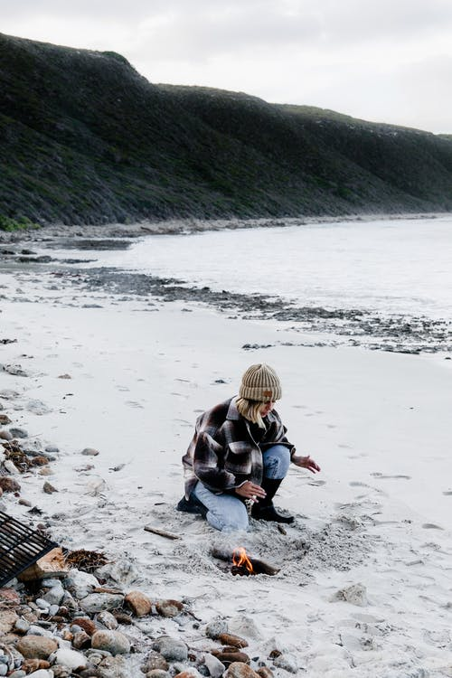 Full body of young female in warm clothes and hat sitting on sandy beach and warming near bonfire