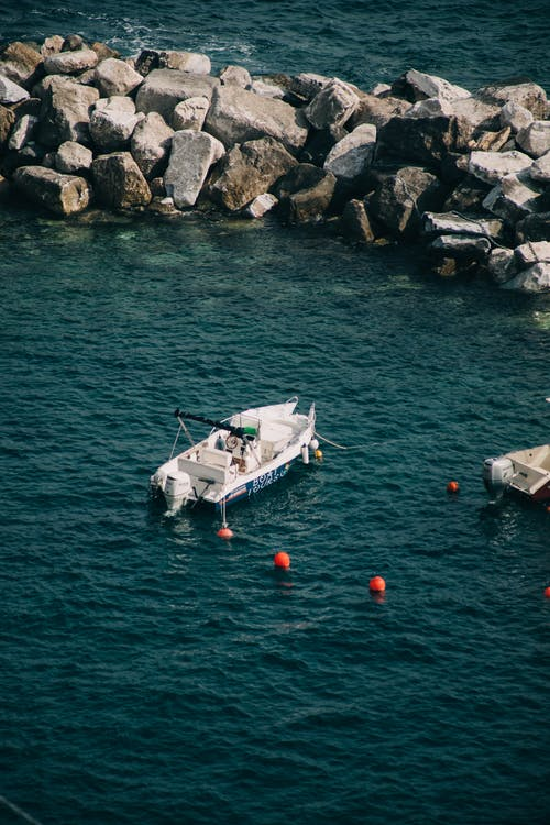 From above of small motorboat floating on sea with blue water near pile of rough rocks