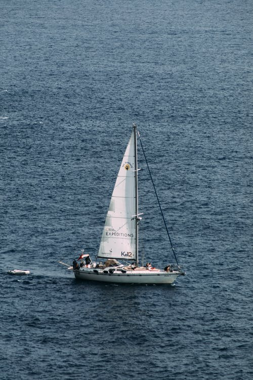 Small yacht with white sail floating in vast sea with blue rippling water in sunny day