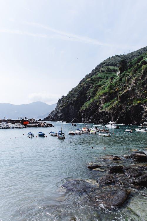 Boats on water near rocky cliff
