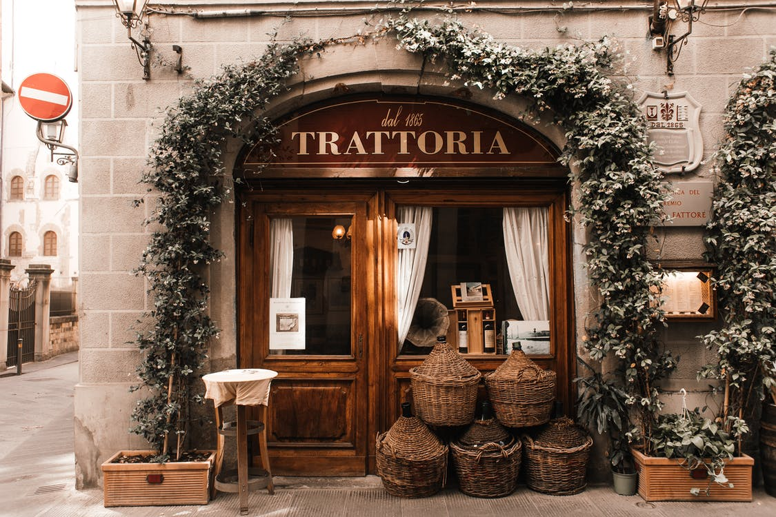 Exterior of cozy Italian restaurant with wooden door and entrance decorated with plants