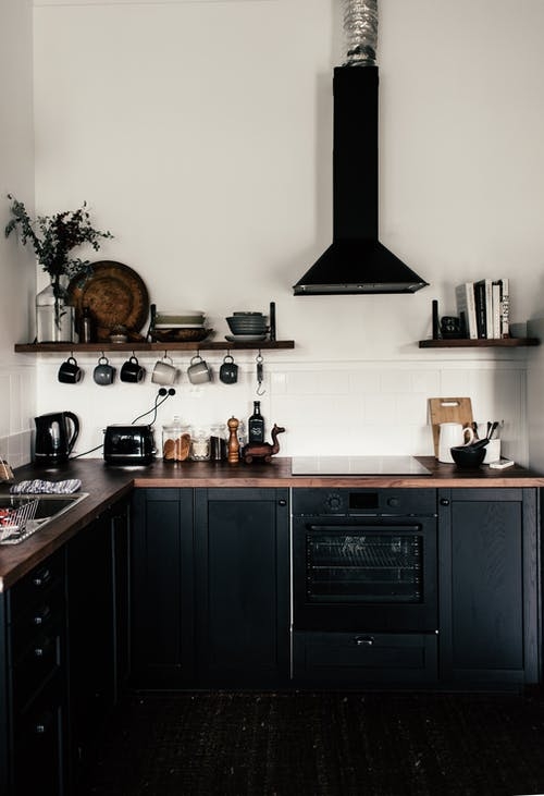 Interior of contemporary kitchen with black wooden cupboards and shelves with various utensils and appliances