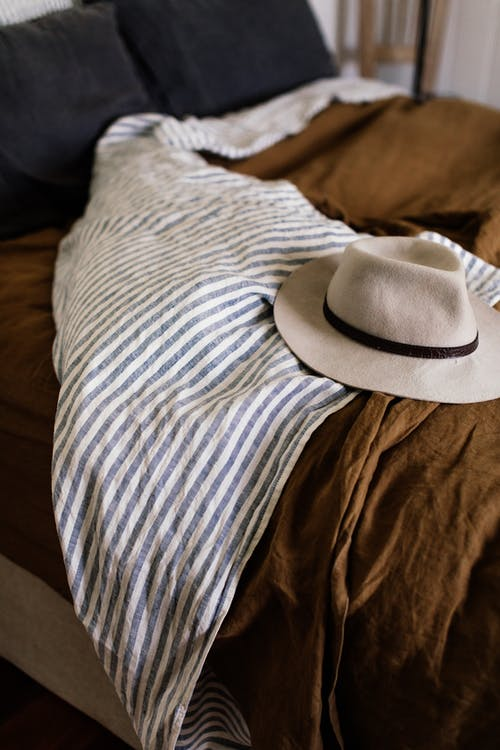 White hat on unmade bed