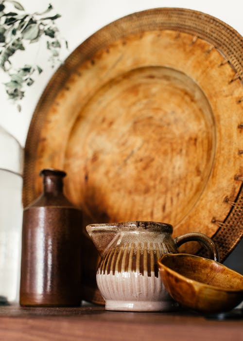 Old vintage ceramic teapot and bowl with bottle on wooden shelf against aged wooden tray