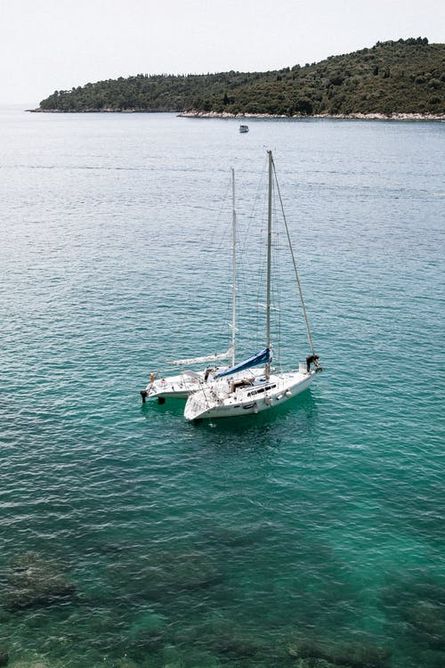 From above of white sailboats floating on rippling turquoise sea water near coast with green trees