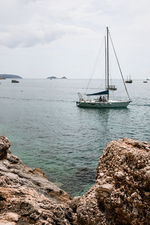 Amazing view of calm turquoise sea water with sailboats floating on surface under cloudy sky