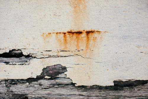 Textured background of weathered shabby cracked aged surface of old wall with plaster