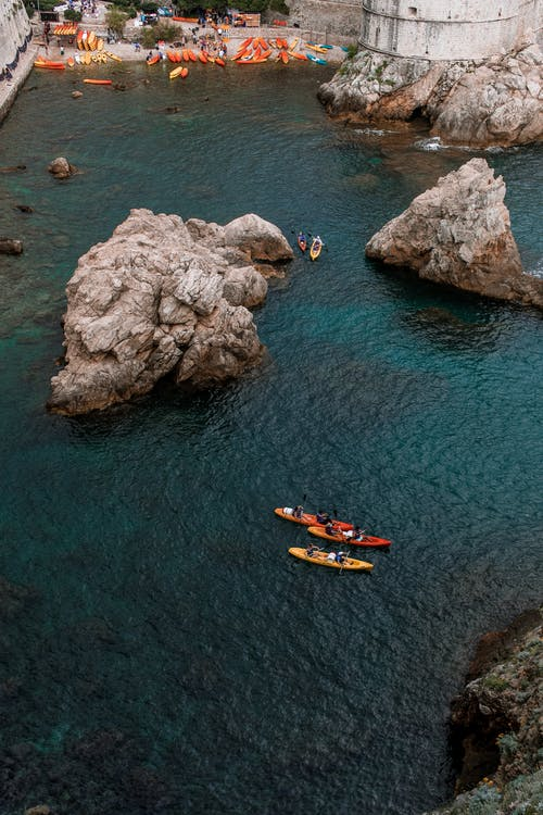 From above of nautical transport on Adriatic Sea with rocks near medieval fortress in Croatia