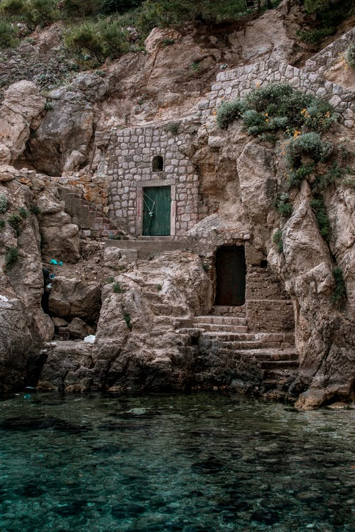 Aged masonry fortress facade with doors and green plants on mountain near rippled Adriatic Sea in Europe