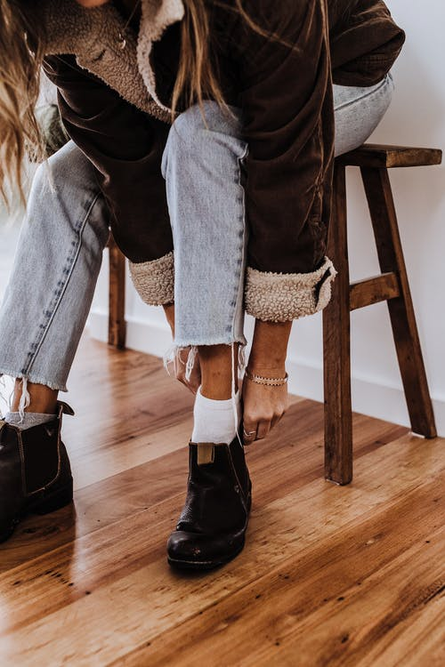 Crop stylish woman putting on boots in house