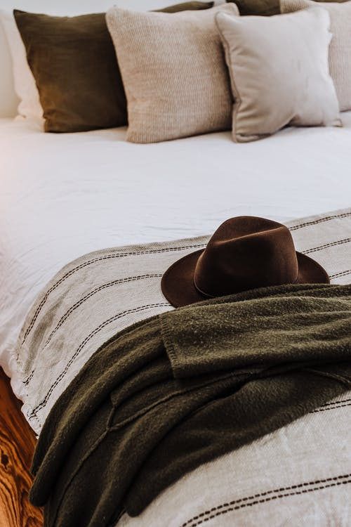 Felt hat on soft bed with decorative cushions