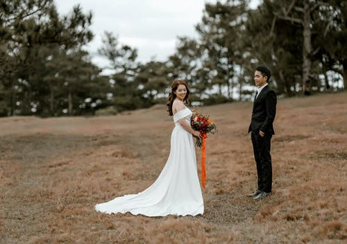 Full body of Asian groom in elegant suit standing with hands in pockets near bride in wedding dress with hem and bouquet in hands with green trees on blurred background