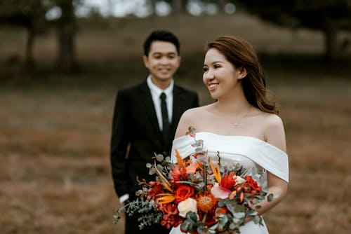 Happy blurred Asian groom standing behind bride in wedding dress and bouquet of flowers in hands while celebrating wedding in nature