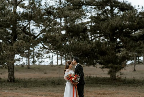 Side view of groom in suit kissing bride with flowers on forehead while standing on grassy field near trees during wedding celebration