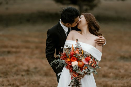 Loving Asian groom and bride with bouquet of flowers wearing wedding outfits kissing while standing in nature with blurred background in daylight