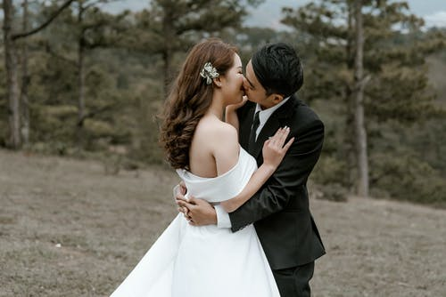 Asian bride and groom kissing in forest
