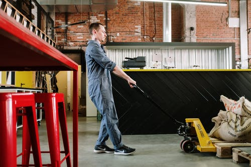 Man in Blue Denim Jacket and Blue Denim Jeans Holding Black and Yellow Hand Truck