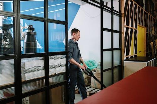 Man in Black Button Up Shirt Standing Beside Glass Window
