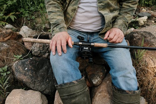 Person in Green and Brown Camouflage Jacket and Blue Denim Jeans Holding Black and Brown Rifle