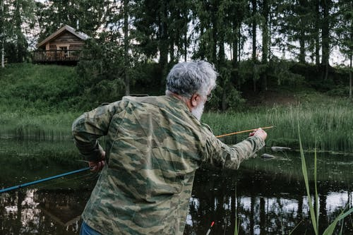 Man in Green and Brown Camouflage Jacket Fishing on River