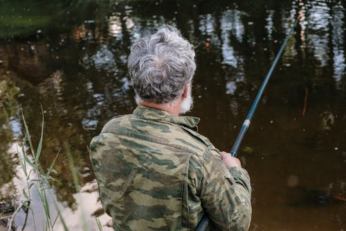 Man in Green and Brown Camouflage Jacket Standing Near Body of Water