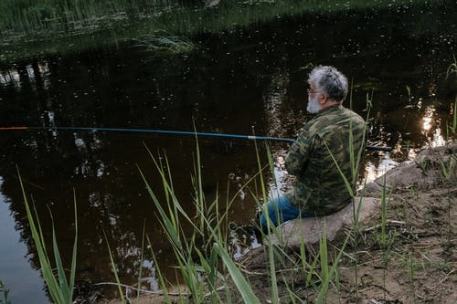 Man in Green and Brown Camouflage Jacket Sitting on Ground Near Lake