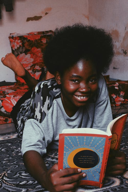 Cheerful young African American woman with curly black hair lying on bed with book and looking at camera