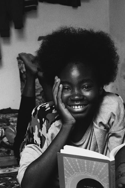 Black and white of smiling African American woman with afro hairstyle lying in room and holding book in hand and looking at camera
