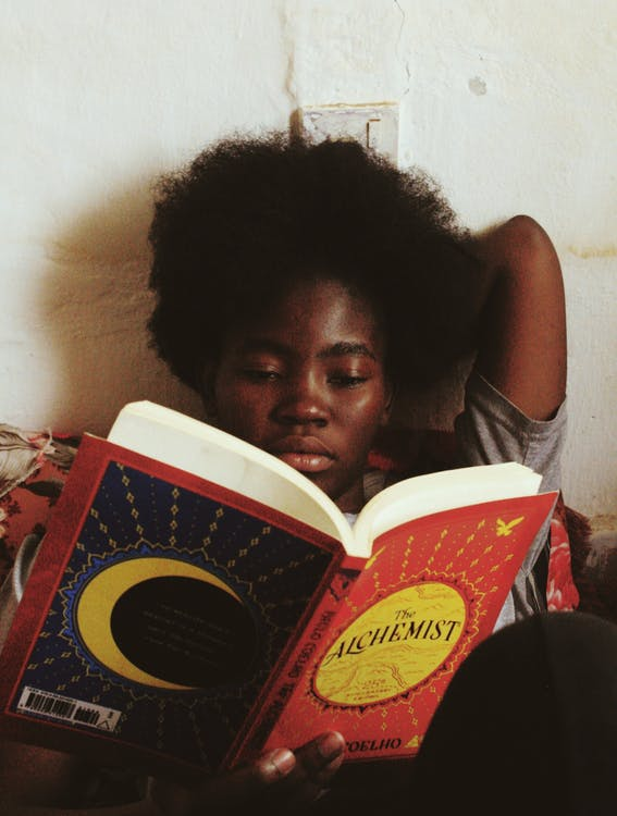 Concentrated African American female with afro hairstyle in casual clothes lying and reading book at daytime