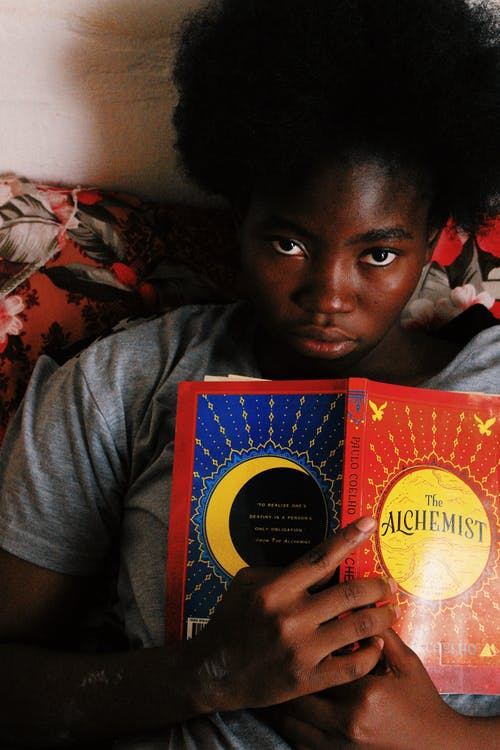 African American young female with curly black hair holding book in hands and looking at camera at home