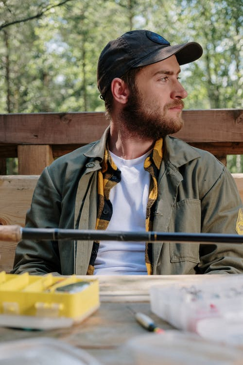 Man in Brown Jacket Sitting on Brown Wooden Bench