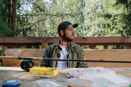 Man in Gray Jacket Sitting on Brown Wooden Picnic Table