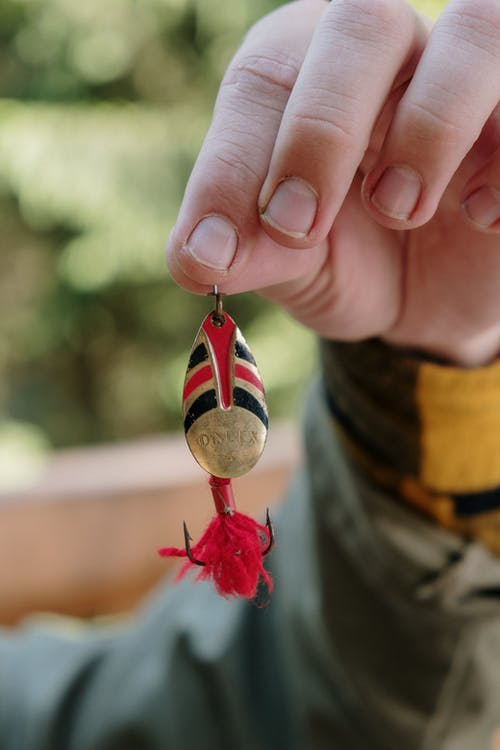 Person Holding Red and White Heart Ornament