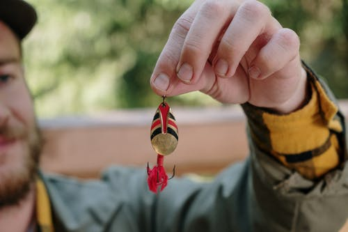 Person Holding Red and Yellow Heart Ornament
