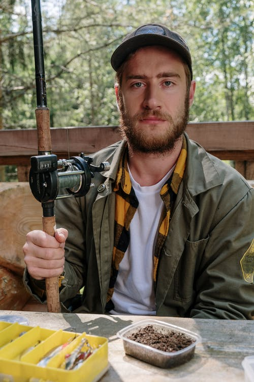 Man in Brown Jacket Holding Black and Gray Camera