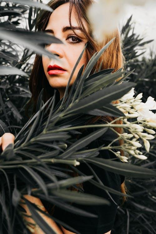 Woman in Black Shirt Standing Beside White Flowers