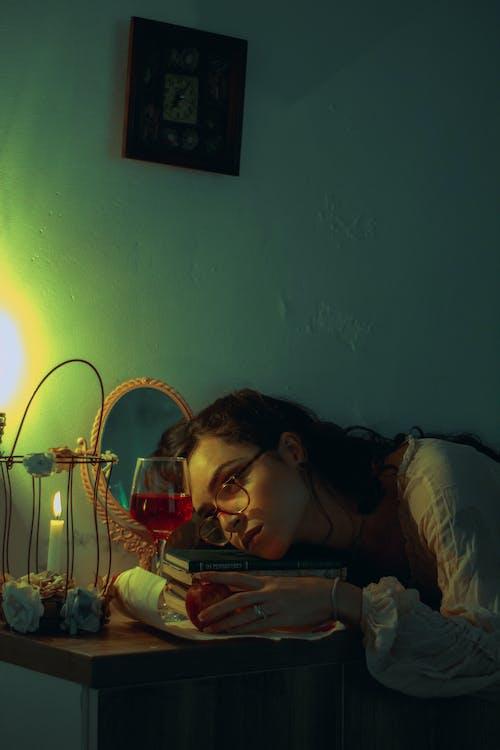 Woman in Black Framed Eyeglasses Lying on Bed