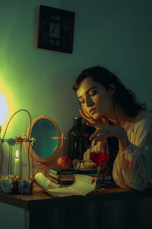 Woman in White Shirt Sitting Beside Table With Candles