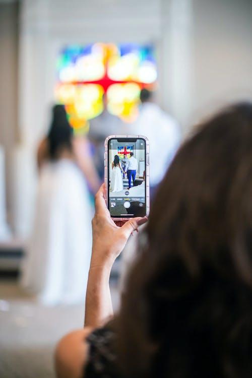Anonymous woman taking photo of wedding